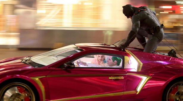 Batman on top of Joker and Harley Quinn's car