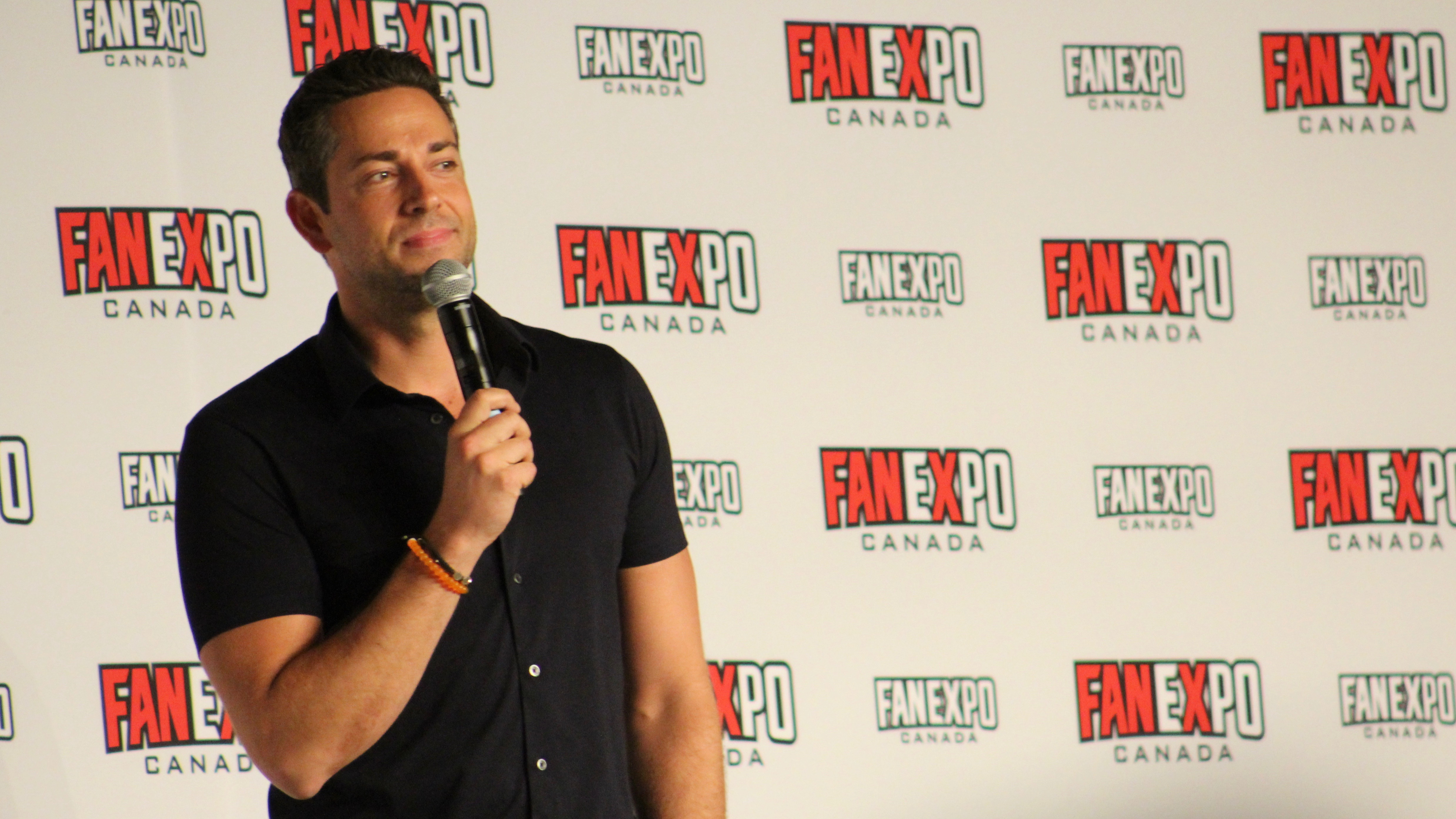Zachary Levi with a microphone at his Q&A panel at FanExpo Canada in Toronto on August 24, 2019.